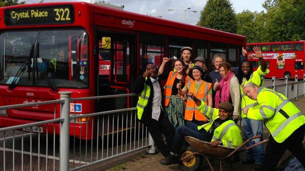 People in wheelbarrow by bus