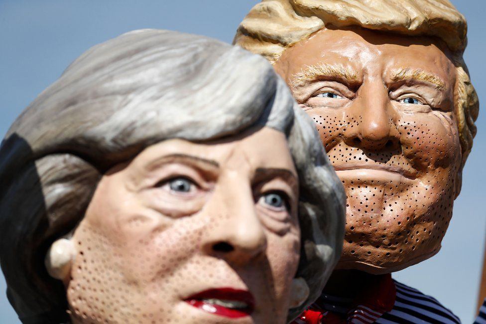 Anti-capitalism activists wearing masks of UK Prime Minister Theresa May (L) and US President Donald Trump protest in Hamburg, 6 July
