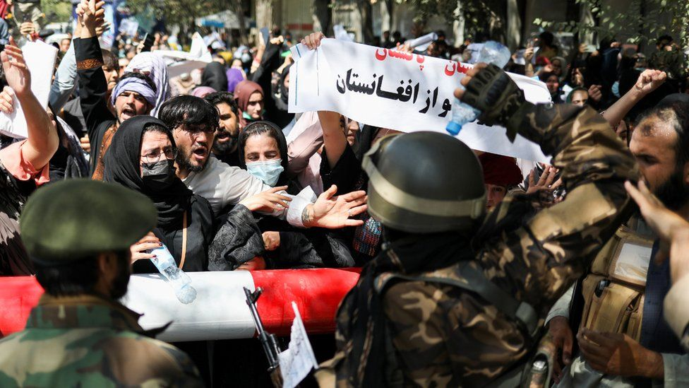 Taliban soldiers stand in front of protesters during the anti-Pakistan protest in Kabul