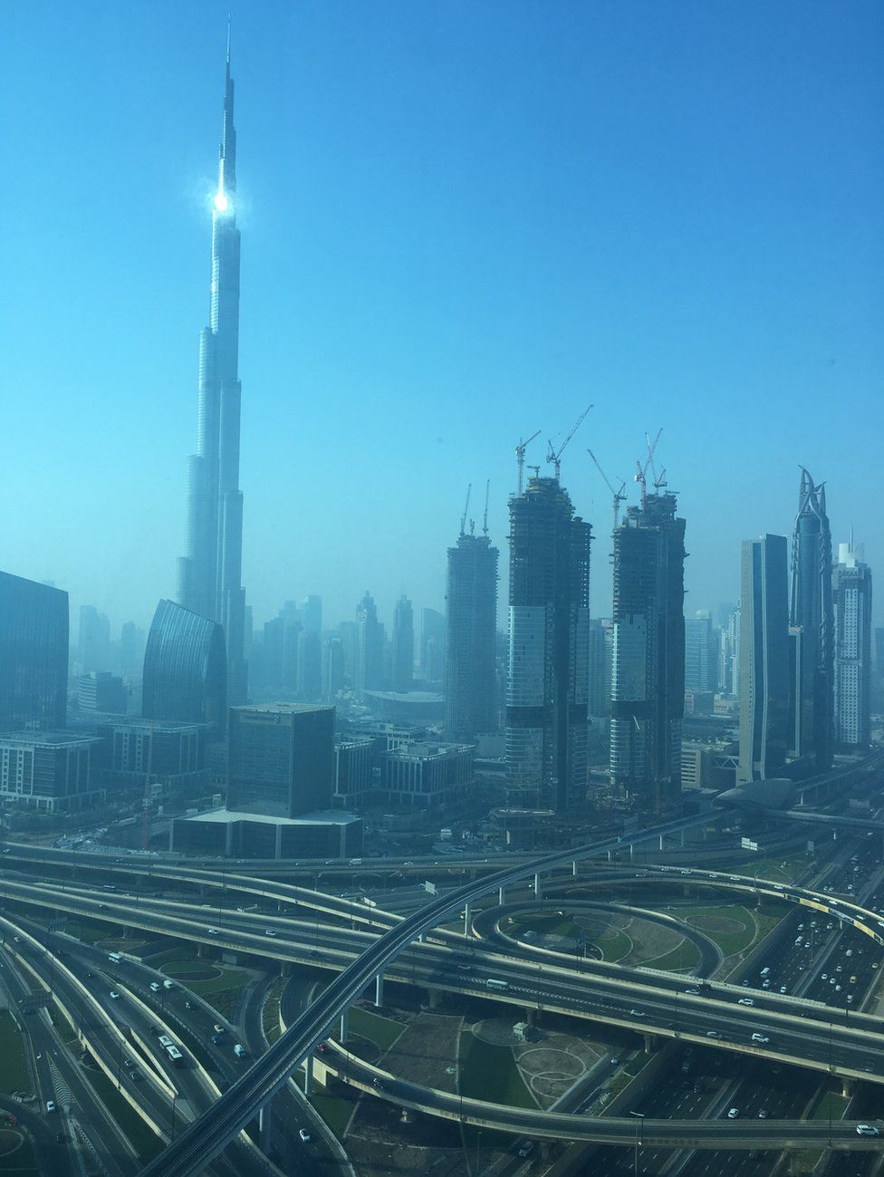 A blue light over the towers and empty roads of Dubai