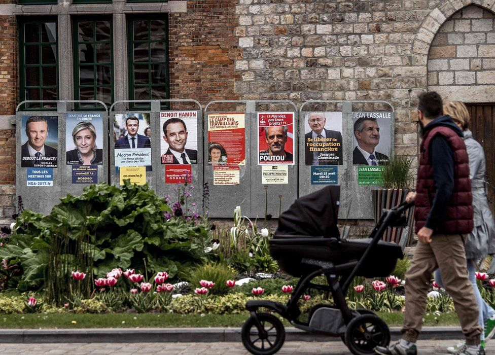 People walk past campaign posters of French presidential election candidates in Bailleul, northern France. 21 France