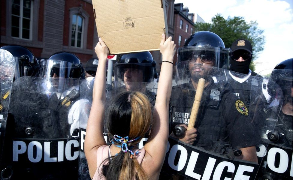 A protester squares up to riot police in Lafayette Square Park in Washington, DC, 30 May 2020