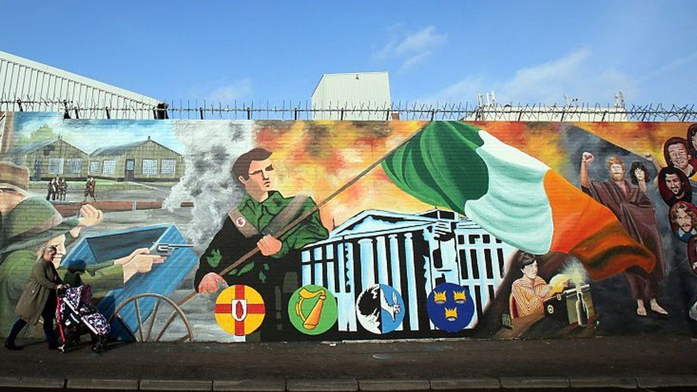 A woman with a pushchair walks past murals on the Falls road in west Belfas