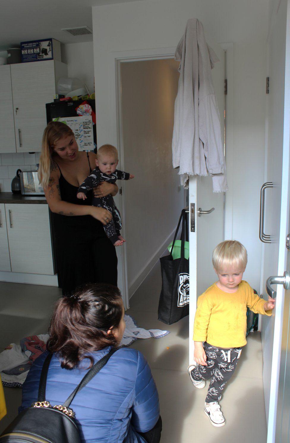 A woman crouches down to greet a little boy