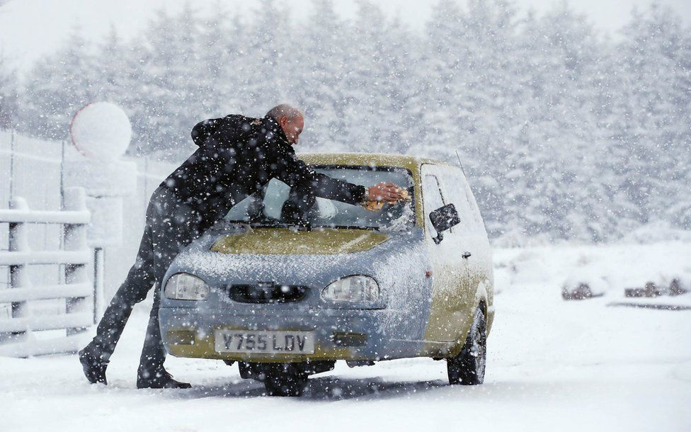 The owner of a three-wheeled Reliant Robin car battles snow
