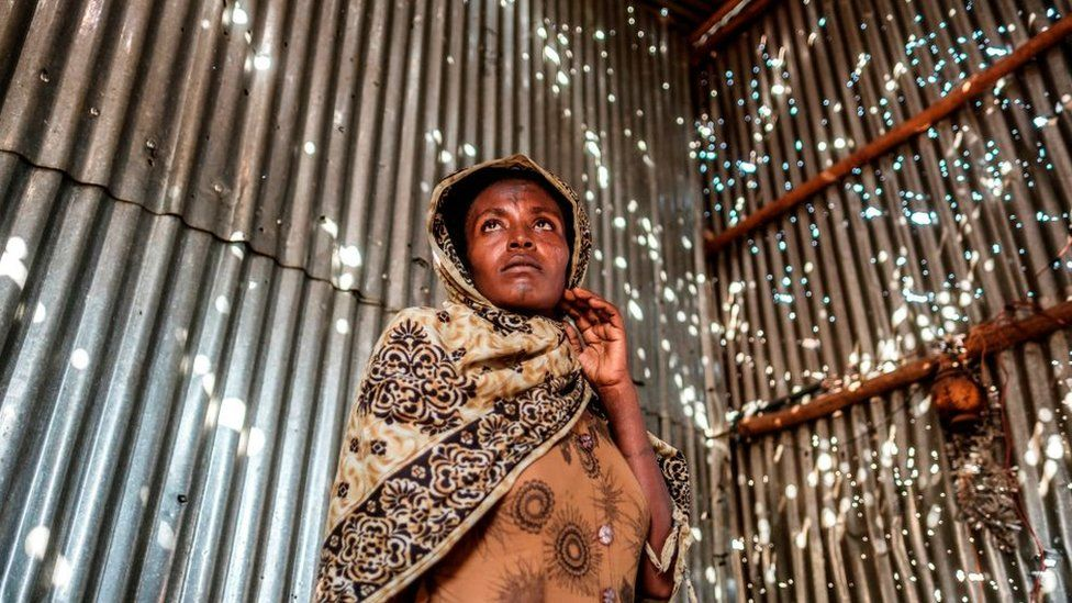 A woman stands in a metal sheet room that was damaged by shelling, in Humera, Ethiopia, on November 22, 2020.