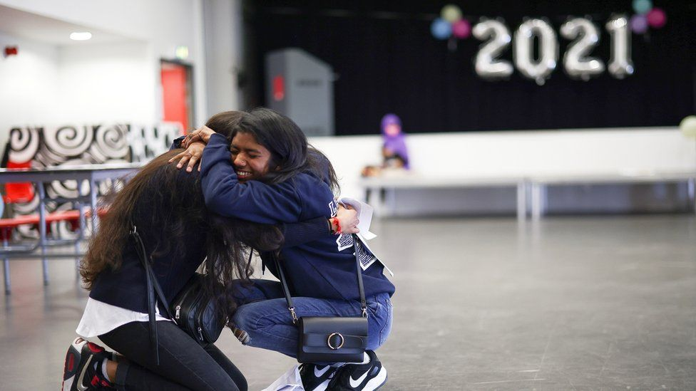Students hug after receiving their results at Ark Academy in London