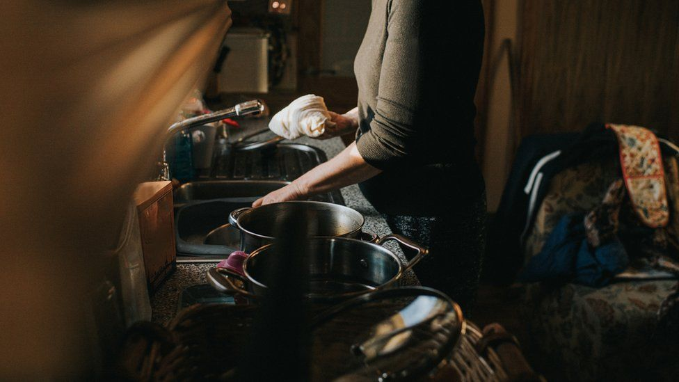 Woman at a kitchen sink stock image