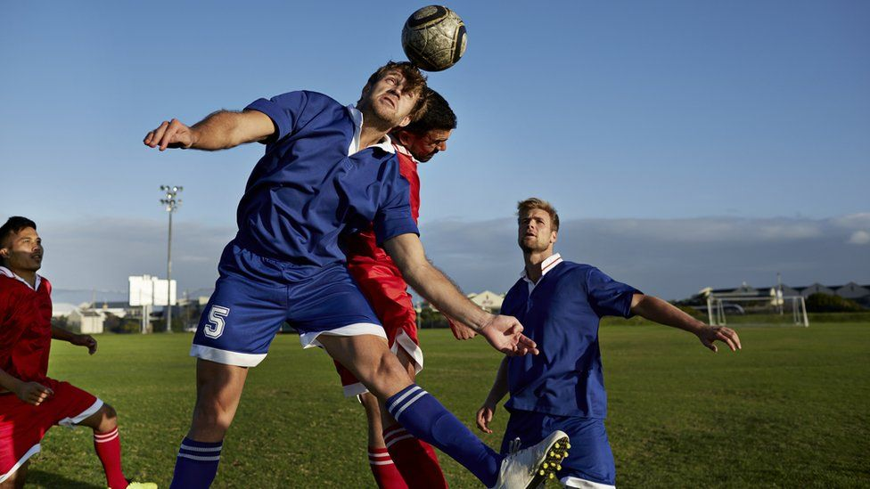 Male footballers going up to head a ball
