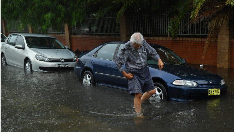 A man wades through floodwater in Sydney, Australia