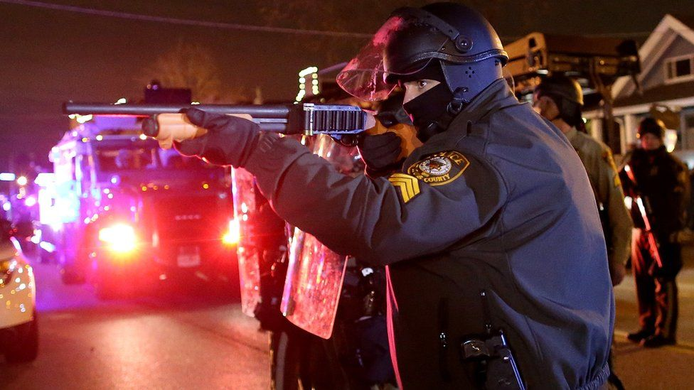 A police officer points a shotgun at protestors during a demonstration in Ferguson, Missouri.