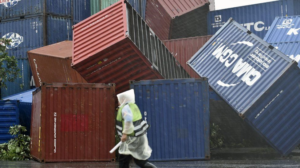 A man walks past downed shipping containers at the Kaohsiung Harbour as typhoon Meranti lashed southern Taiwan on September 14, 2016.
