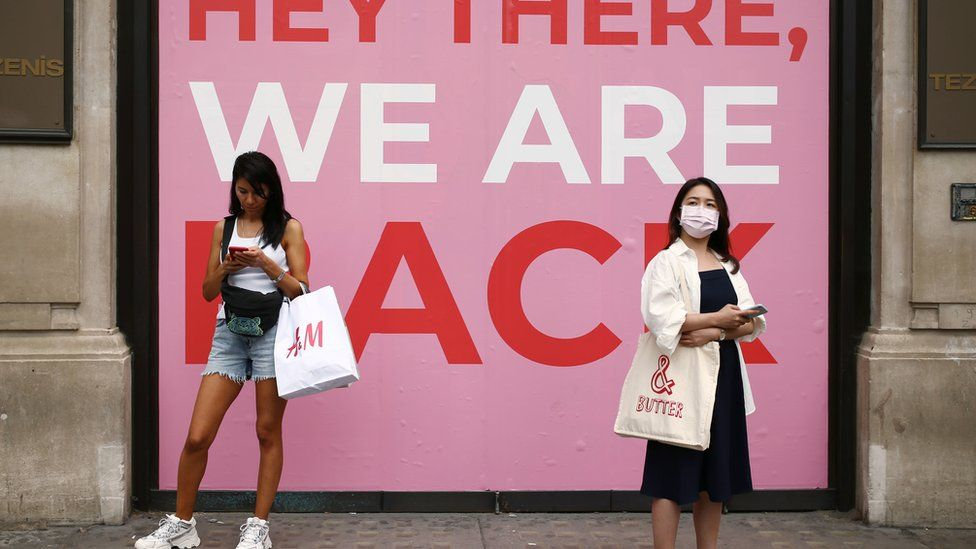 Two people with facemasks outside shop