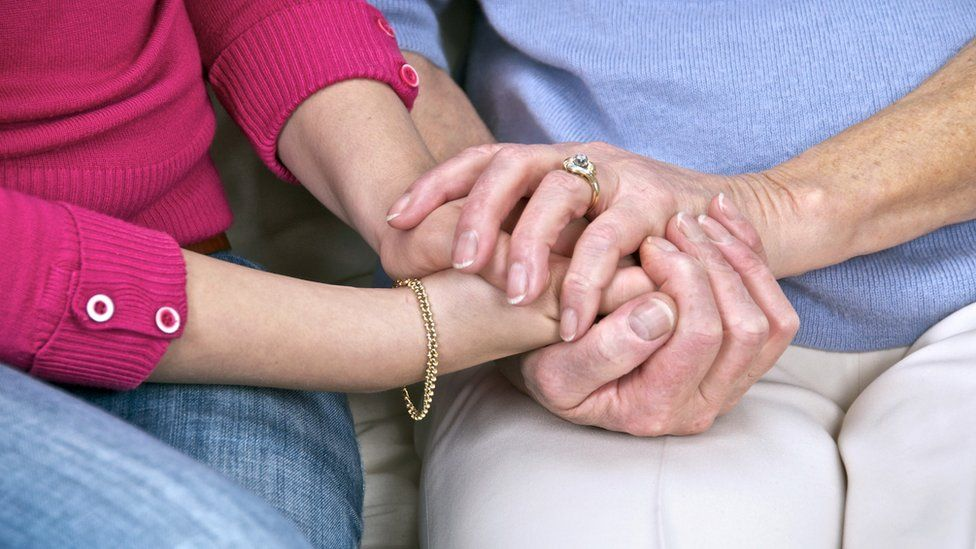 An elderly person holds hand with carer