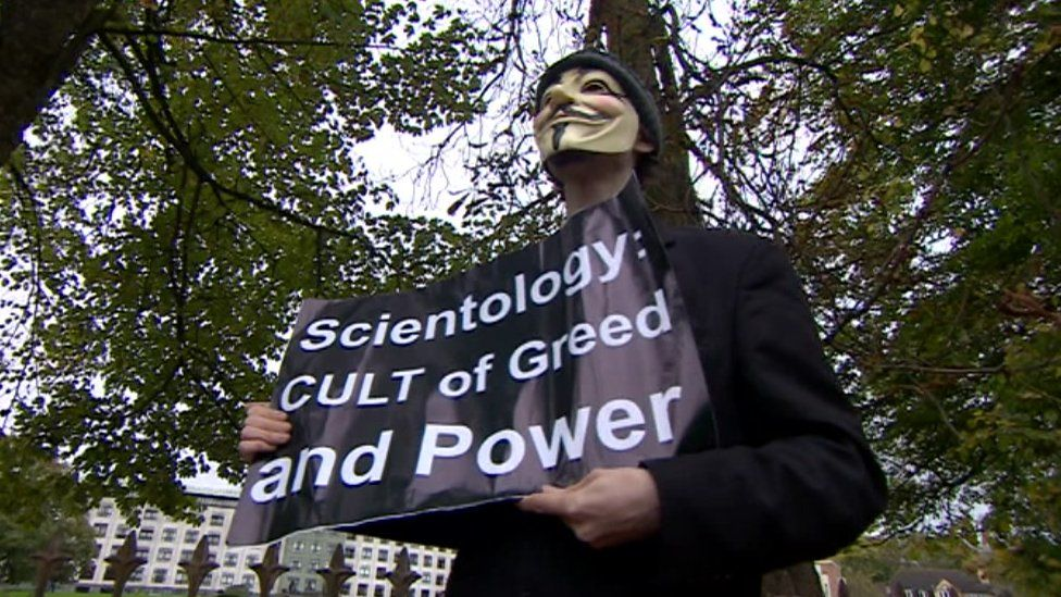 "A protester holds a sign reading ""Scientology: Cult of greed and power"""