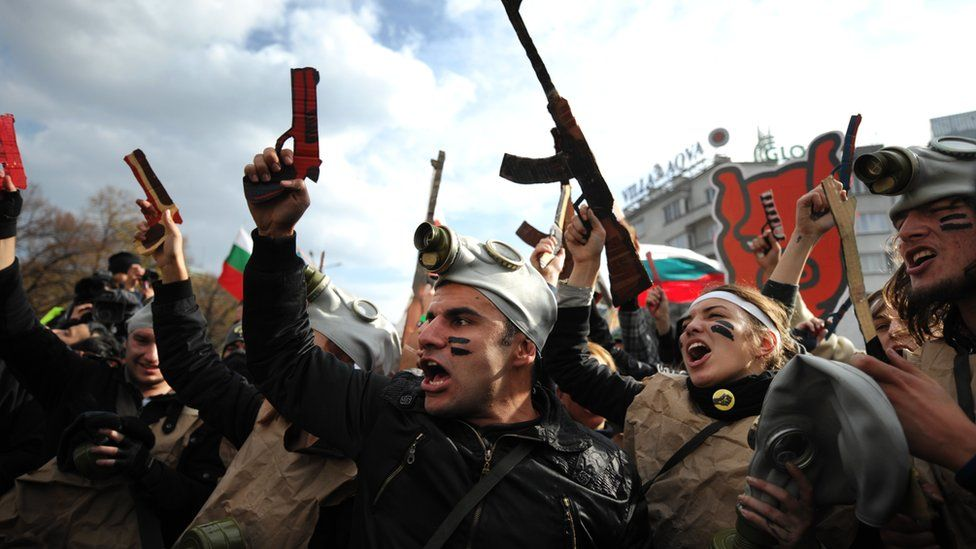 Students with cardboard weapons participate in a performance during an anti-government protest in front of the Bulgarian parliament in Sofia on 20 November 2013.