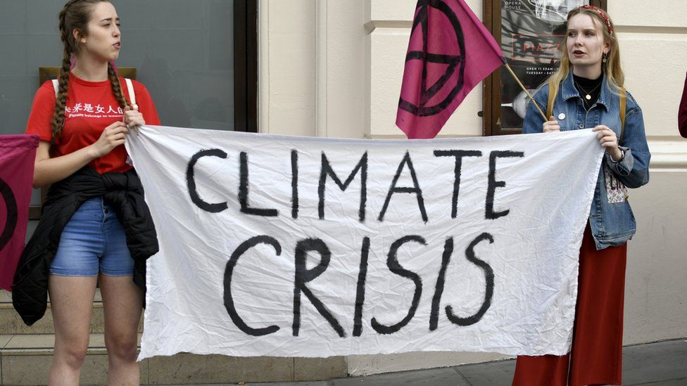 Extinction Rebellion activists hold a banner and a placard outside the Royal Opera House main entrance during a protest in London