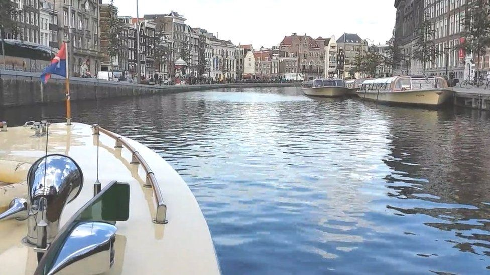 Prow of Prinses Irene sailing down canal with cityscape in background