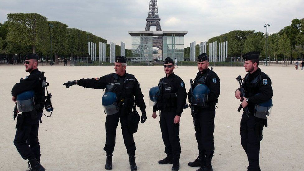 French policemen stand in front of the Eiffel tower in Paris on 22 April, 2017.