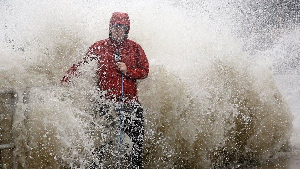 A news reporter doing a stand up near a sea wall in Cedar Key, Florida is covered by an unexpected wave as Hurricane Hermine nears the Florida coast, Thursday, 1 September 2016.