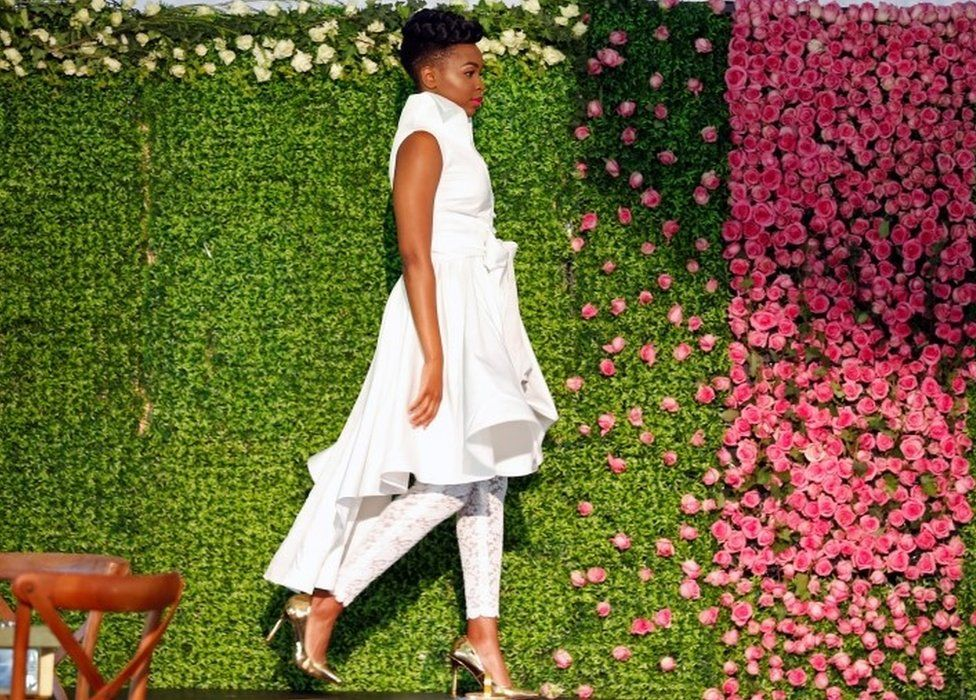 """A model presents a wedding dress creation before a TV broadcast of Britain""""s Prince Harry and Meghan Markle""""s royal wedding at the Windsor Golf Hotel and Country Club in Nairobi, Kenya May 19, 2018"""