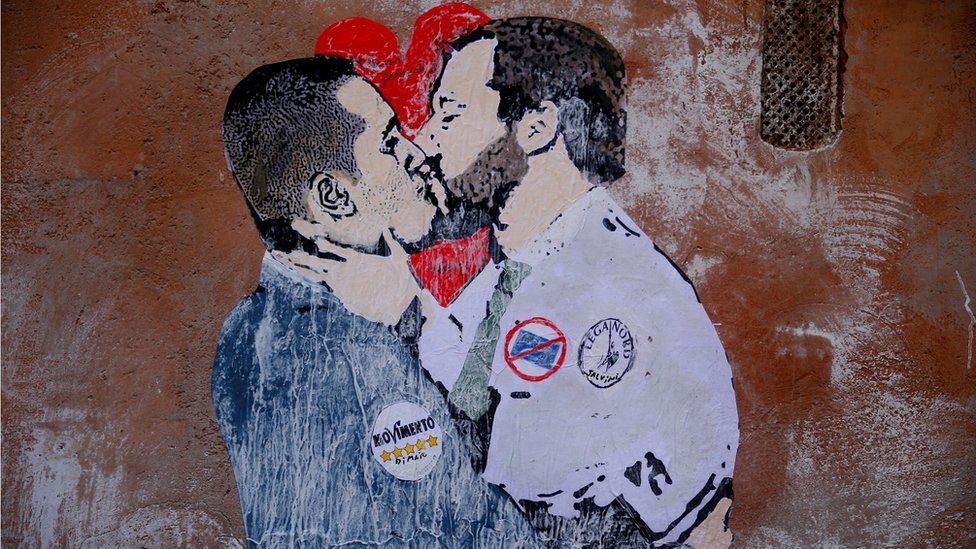 A mural depicting Northern League's leader Matteo Salvini (R) and 5-Star Movement leader Luigi Di Maio kissing is seen in Rome,