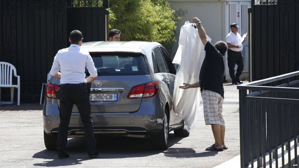 A man holds clothes on a hanger as he arrives at the villa of the Saudi king in Vallauris