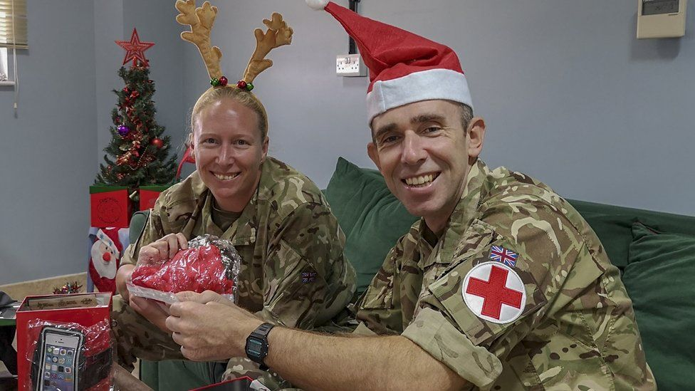 Two members of the armed forces wearing Christmas-themed headwear