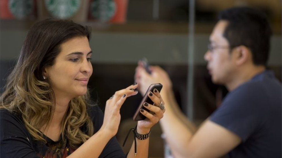 A woman checks her cell phone at a coffee shop in Sao Paulo on 17 December 2015