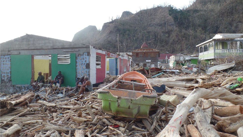 A boat can be seen lying amid rubble in Soufriere