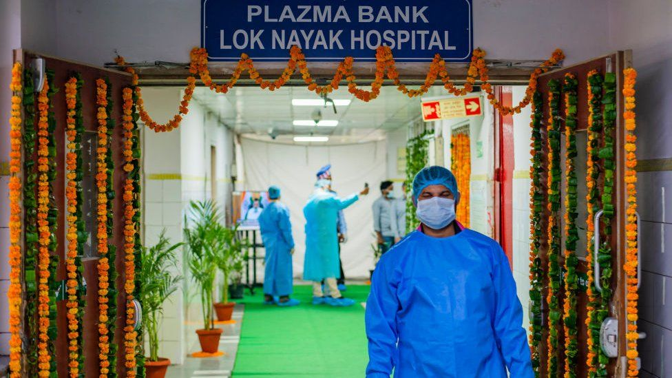 A technician wearing a personal protective Equipment suit (PPE) is seen coming from the Plasma Bank. Delhi's second plasma bank started today. Delhi has the highest Covid-19 recovery rate within the whole of India