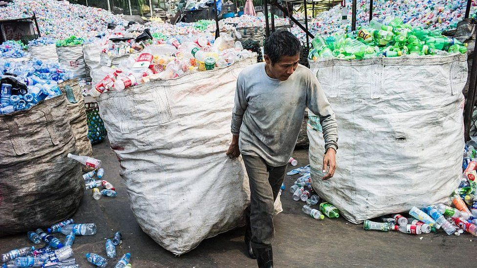 A Chinese worker pulls a bag of plastic bottles being recycled
