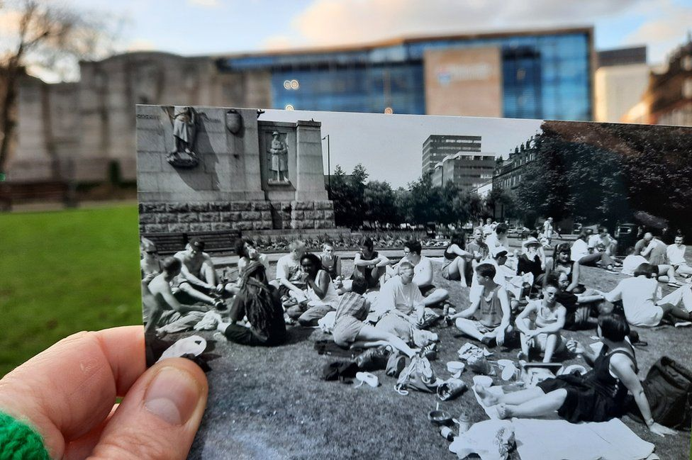 Julie holding a picture of people having a picnic in the centre of Newcastle