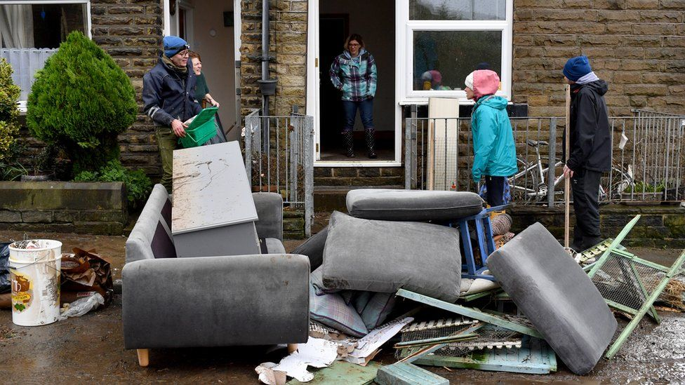 Residents stand outside with ruined furniture in West Yorkshire