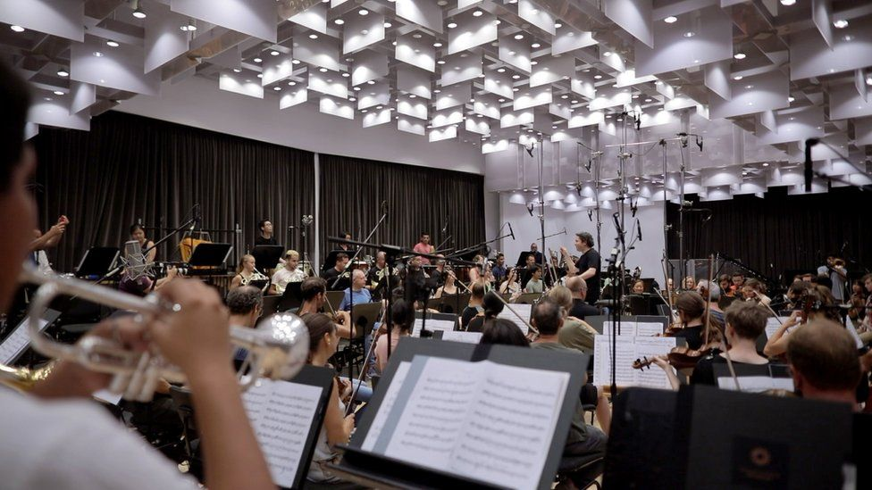 Here, Gustavo Dudamel leads rehearsals with the orchestra behind the recordings in the films
