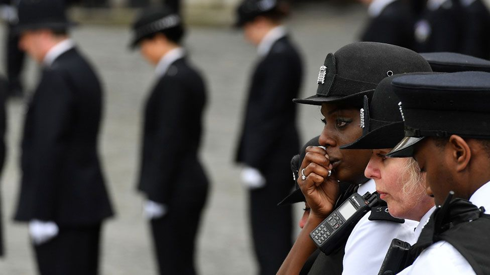 Police officers react as the hearse goes past them