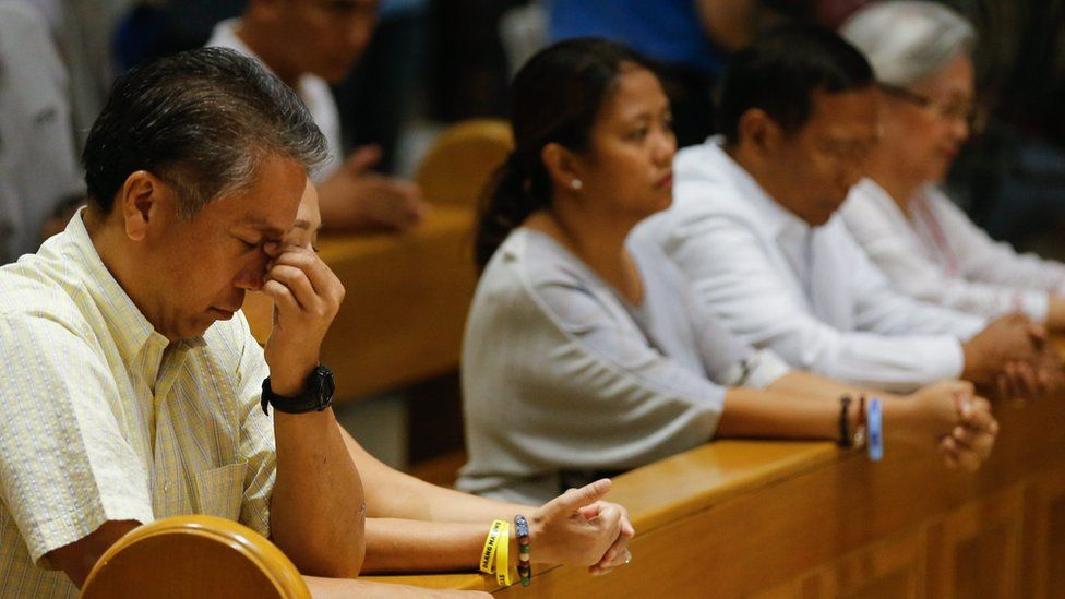 """Manuel """"Mar"""" Roxas III (left) prays in Manila Cathedral, alongside other faithful, including fellow presidential candidate Jejomar Binay (second from right)"""