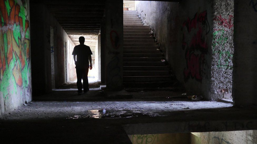 A lone figure walks down a dark hallway in the ruined building, with graffiti on the walls