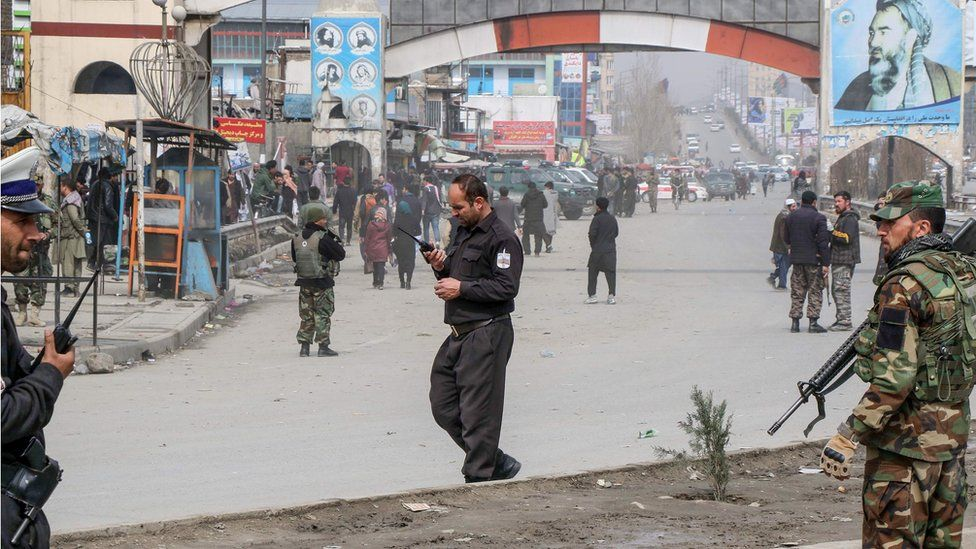 Afghan security forces personnel stand guard on a road near the site of a gun attack that occurred during an event ceremony to mark the 25th anniversary of the death of Shiite leader Abdul Ali Mazari, in Kabul on March 6, 2020.