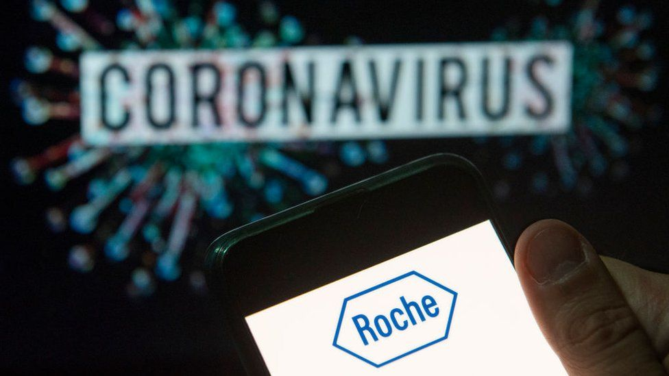 Roche logo seen displayed on a smartphone with a computer model of the COVID-19 coronavirus on the background