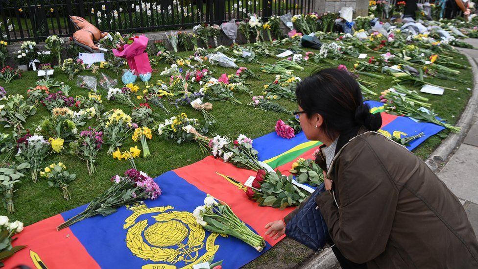 People place flowers with condolence messages outside Windsor Castle
