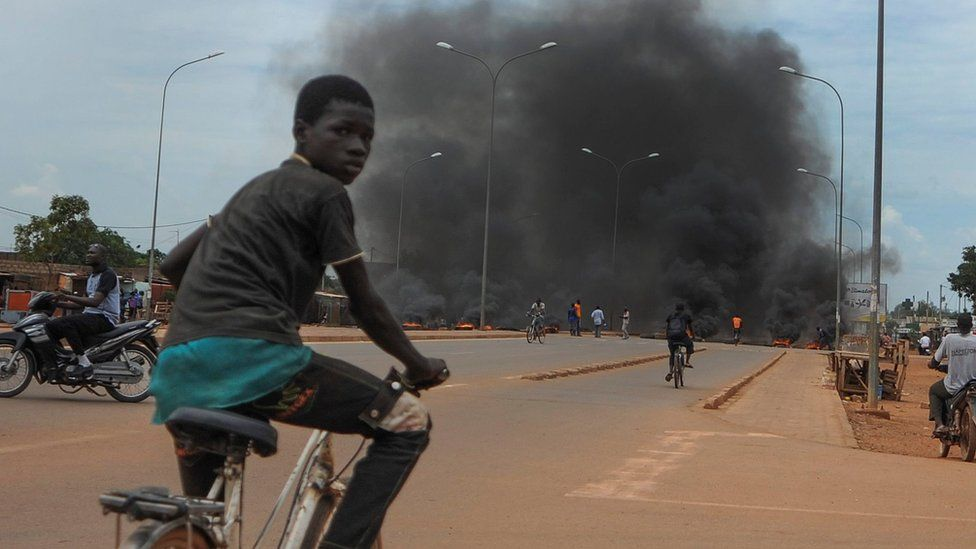 A child cycles in front of a burning barricade in the capital Ouagadougou