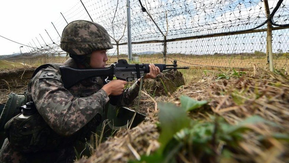 A South Korean soldier stands guard in front of a military fence at a General Outpost (GOP) of the Demilitarized Zone dividing the two Koreas in Cheorwon on October 13, 2015.