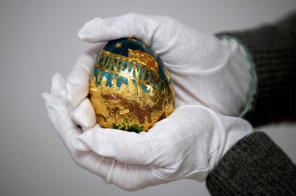 A pair of gloved hands hold an ornate golden egg
