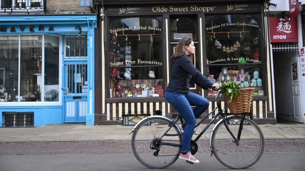 Woman cycling past small shops in Cambridge