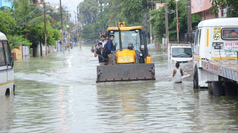 A digger on a flooded road