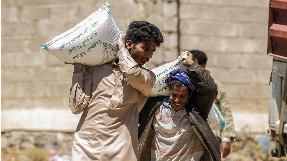 Displaced Yemenis carry sacks of food supplies on outskirts of Sanaa (16/03/17)
