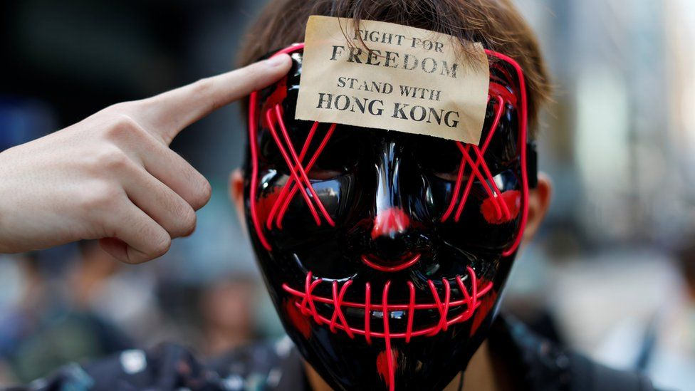 """A masked anti-government protester points to a sign on his forehead which says """"stand with freedom, stand with Hong Kong"""""""