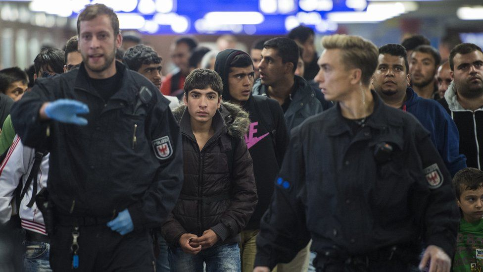 German police officers lead a group of refugees through the Schoenefeld regional railway station near Berlin.