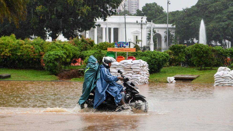 Pengendara sepeda motor melintasi banjir di Jalan Medan Merdeka Barat, Jakarta, Minggu (2/2/2020).